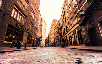 Photo: Stone Street - New York's first paved street   Stone Street is a narrow cobblestone alley that was first developed by Dutch colonists in the 1600s. Its claim to fame is that it is New York City's first paved street and as such it is recognized as a historic landmark.  It's the main part of an area currently known as the Stone Street Historic District. Nestled among skyscrapers in the Financial District, it's something of a time machine back into another era of New York City's history. The street is the site where British merchants traded and sold goods, where American colonialists passionately spoke of independence and where tracts of land were purchased and sold (completely disregarding the earlier inhabitants of the area).  The Dutch West India Company first sold this area to European property owners in the mid 1600s. It was around 1658 that the street was paved. The name Stone Street actually came about in the late 1700s. Prior to being named Stone Street, this alley was called Hoogh Straet and then Brouwer Street and also spent some time as Duke Street. Since the street is so close to the waterfront, it was the site of a tremendous amount of commercial activity for two centuries.  In the mid 1800s, the area was destroyed by the Great Fire. Even though the Great Fire leveled hundreds of buildings in the area, the Stone Street district bounced back due to New York City having the leading maritime port in the country. However, in the mid twentieth century the area saw a decline due to maritime activity moving to the west side of Manhattan. In the mid 1990s, funding was secured to restore the area back to its former glory.  —-   Shot with the Sony a99 a few days ago on a bitterly cold winter day here in New York City, I can't think of a better time to experience this historic alley. It comes to life in the summer when it is full of chairs and tables linked to the many dining establishments that now inhabit the buildings along Stone Street. But it's in the win