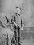 jongen in nette kleding naast een fauteuil met tapijt er over