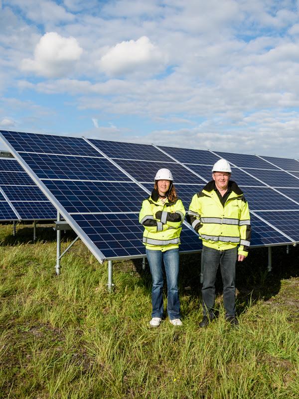 Deux personnes debout devant de grands panneaux solaires dans un champ