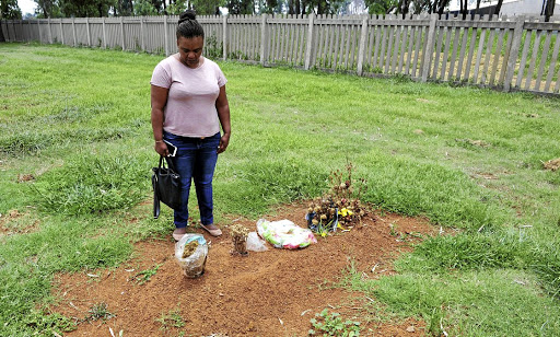 Jeanette Brown stands next to the grave of her brother Elwon Scharnick who was given a pauper's funeral in Meyerton. / Veli Nhlapo
