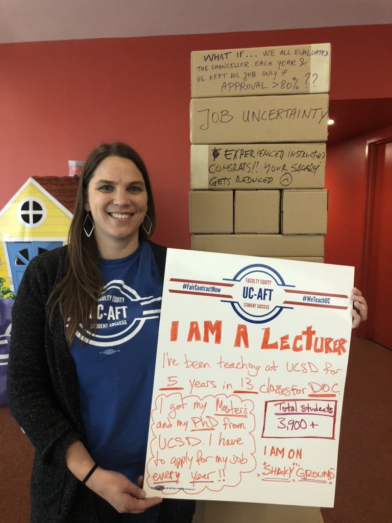 "The image shows a woman with long brown hair. She is wearing a blue UC-AFT t-shirt and smiling at the camera. She holds a sign that reads, ""I am a lecturer. I've been teaching at UCSD for 5 years in 13 classes for DOC. I got my Master's and my PhD from UCSD. I have to apply for my job every year!! Total students: 3,900+ I am on ""shaky"" ground."""