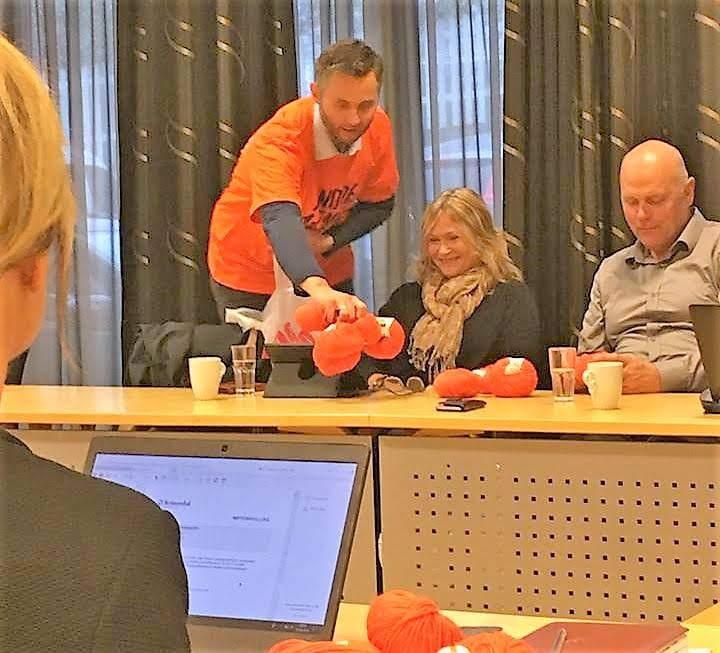 Bilde av ordfører som deler ut garn til oransje skjerf