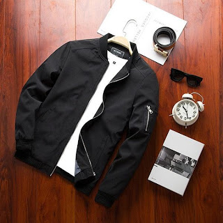 Plain black bomber jacket with a black collar and a zipper pocket on left sleeve with a belt, a sunglasses, an alarm clock and a notebook on a wooden floor background