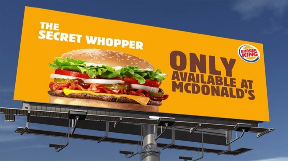 """A Burger King billboard with a hamburger, yellow background and text """"The Secret Whoppers only at McDonald's""""."""