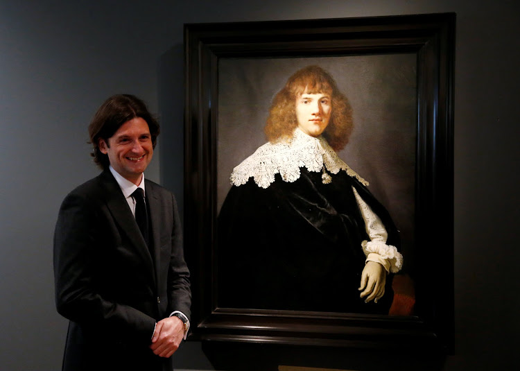 "Dutch art dealer Jan Six stands next to a Rembrandt painting called ""Portrait of a Young Man"" at Hermitage Amsterdam, Netherlands, May 16, 2018."