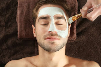 a male receiving a face mask during a facial