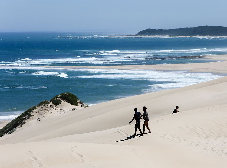Visitors first climb a giant sand dune to get to the beach at Sardinia Bay