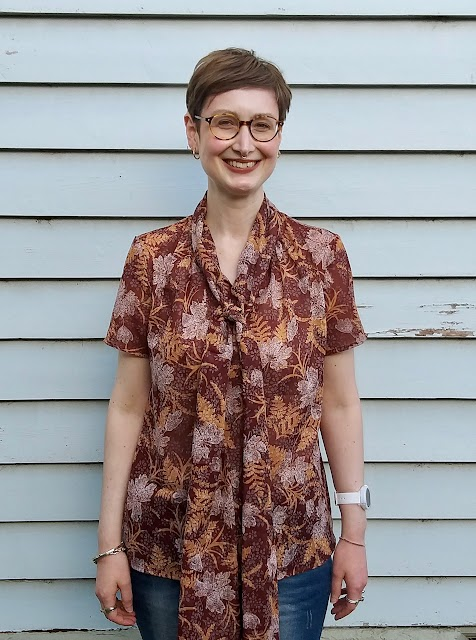 Siobhan stands in front of a blue weatherboard wall. She wears an earthy brown, fern-print short sleeve blouse with comically large bow at neck. She is smiling.