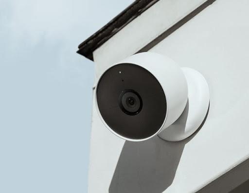 Google Nest Cam を片手で壁に取り付けています。