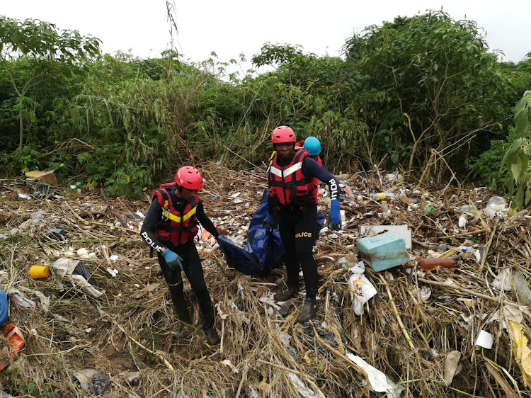 Search and rescue members remove the body of a woman who was recovered under a mass of debris at the Amaoti River, north of Durban, on Tuesday March 14 2019.