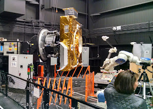 Photo: The back end of a decommissioned weather satellite sits in the Satellite Servicing Capabilities Office at NASA's Goddard Space Flight Center. To the right are prototype robotic controllers that may assist in future refueling missions.