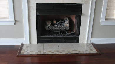 Photo: Picture framed fireplace with custom wood moldings, tile inlay, and boarder. Flooring is engineered Santos Mahogany.