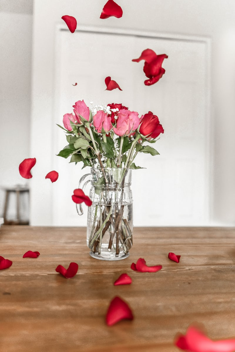 a vase of wilting roses and rose petals falling on the table