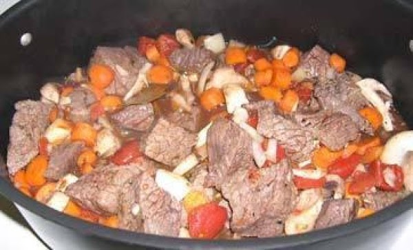 Now add the saved drippings and mix well. Then add the browned potatoes, carrots...