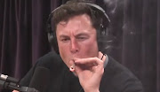 A screen grab of Elon Musk smoking weed during a live webcast with comedian Joe Rogan.