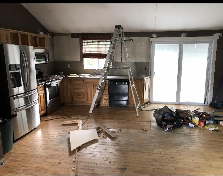 This is the kitchen just getting started for remodel. Dark walls, old weathered wood cabinets and floors.