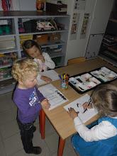 Photo: Kijk zo teken je een kindje. Kinderen van de 2° kleuterklas leren het aan de kinderen van de eerste kleuterklas.
