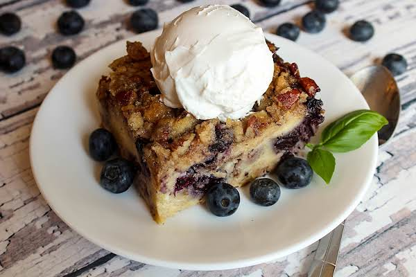 Slice Of Blueberry Crunch Bread Pudding With Whipped Cream And Blueberries.