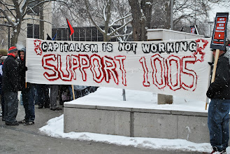 "Photo: Supporters of Steelworkers Local 1005 hold a banner that reads ""Capitalism is not working."""