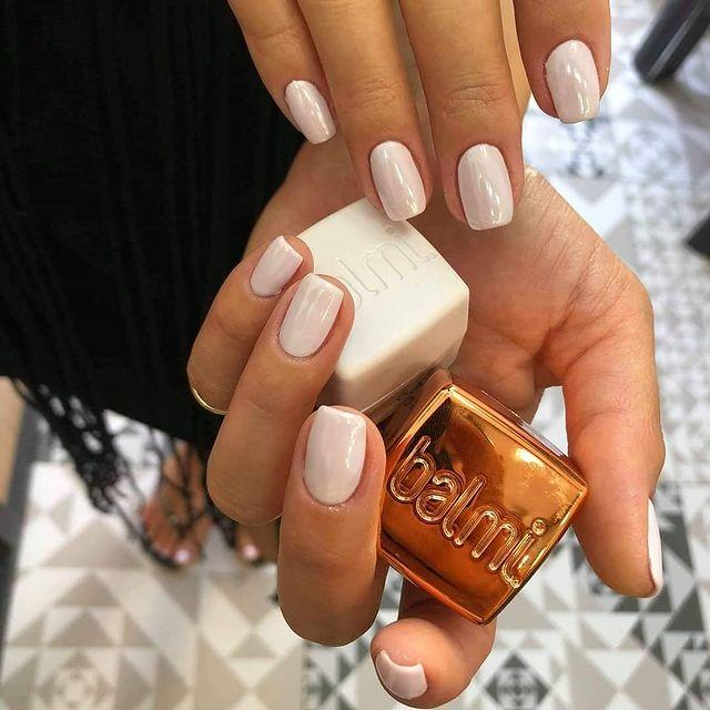 A hand holding a bottle of nail polish Description automatically generated with low confidence
