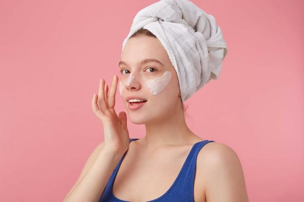 Photo of young nice glad lady with natural beauty with a towel on her head after shower, stands and puts on face cream, looks away. Free Photo