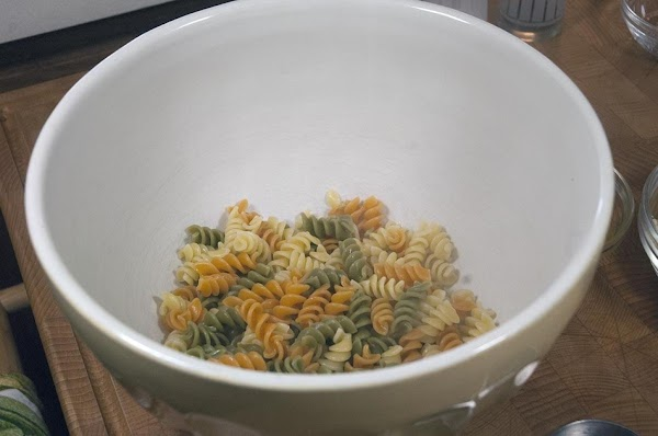 Add the pasta to a large bowl, and reserve.