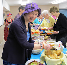Photo: Past chair, Granny Shirley, sports a colorful hat at the Potluck Dinner buffet.
