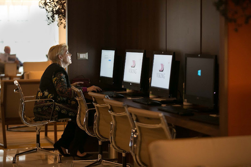 A passenger takes advantage of free Internet in the atrium of Viking Sun.