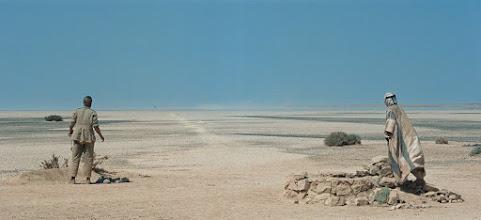 """Photo: A famosa """"cena da miragem"""", com o personagem de Omar Sharif como um pequeno ponto negro observado por Lawrence e seu guia. Notem o caminho branco ao centro criado pela equipe de direção de arte para ajudar o nosso olhar a chegar ao ponto preto."""