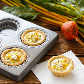 Bite-Sized Golden Beet and Goat Cheese Quiches with Pine Nut Crust.