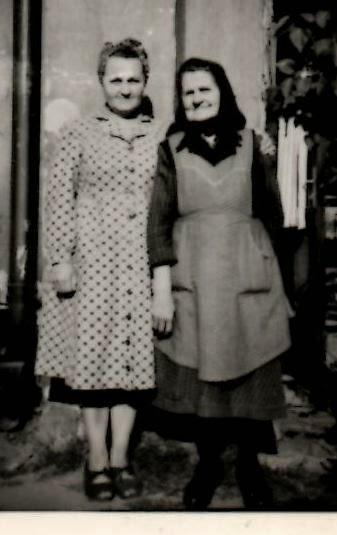 Photo: Szalai Mária nagyanyja Kovács Ignácné Kántor Eszter a képen nevelt lányával, Csizmadia szül. Kántor Margittal: Nagyanyám mesélte, ahogy nőtt a fia, folyton azt kérdezte, mikor jön haza az apa. Nem jött, de még hírt sem kaptak felőle, hiába kerestette őt a nagyanyám a Vöröskereszten keresztül a háború után. Nagyon nehezen éltek sokáig, segélyt sem kaptak, egyedül nevelte az édesapámat. Elbeszéléséből tudom, hogy aratáskor félrészességet vállalt. Úgy kellett dolgoznia, mint a férfiaknak, csak a zsákolást csinálták meg helyette. Sokat dolgozott a gazdáknál, mosást, meszelést vállalt, csakhogy a fia az én apám semmiben ne érezzen hiányt.  Később tudott venni egy kis házat, amibe már mi unokák is nevelkedtünk. Elnézegetem a nagyanyám régi megsárgult papírjait, melyen a háza adásvételi szerződése van, annyi idegen nevet olvasok, akik már rég nem élnek, akiktől a nagyanyám darabokban vett meg földet, ahogy mondta: egy kis búzának, kukoricának, meg krumplinak, amiből élni tudtak.