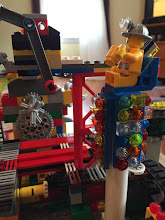 Photo: The arm going up and to the left can be swung down to disable the fingers so the cams spin freely. Yellow Lego dude is the operator.
