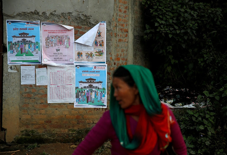 A woman walks past the instruction posters near the polling station a day ahead of the parliamentary and provincial elections at Chautara in Sindhupalchok District, Nepal November 25, 2017. Picture: REUTERS/ NAVESH CHITRAKAR