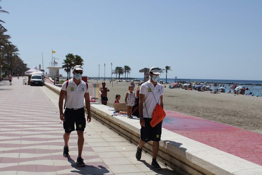 Auxiliares de playa informando de la obligatoriedad de usar la mascarilla.