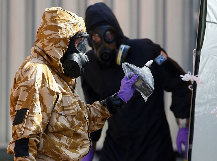 Forensic investigators, wearing protective suits, emerge from the rear of John Baker House, after it was confirmed that two people had been poisoned with the nerve-agent Novichok, in Amesbury, Britain, on July 6, 2018. Picture: REUTERS/HENRY NICHOLLS