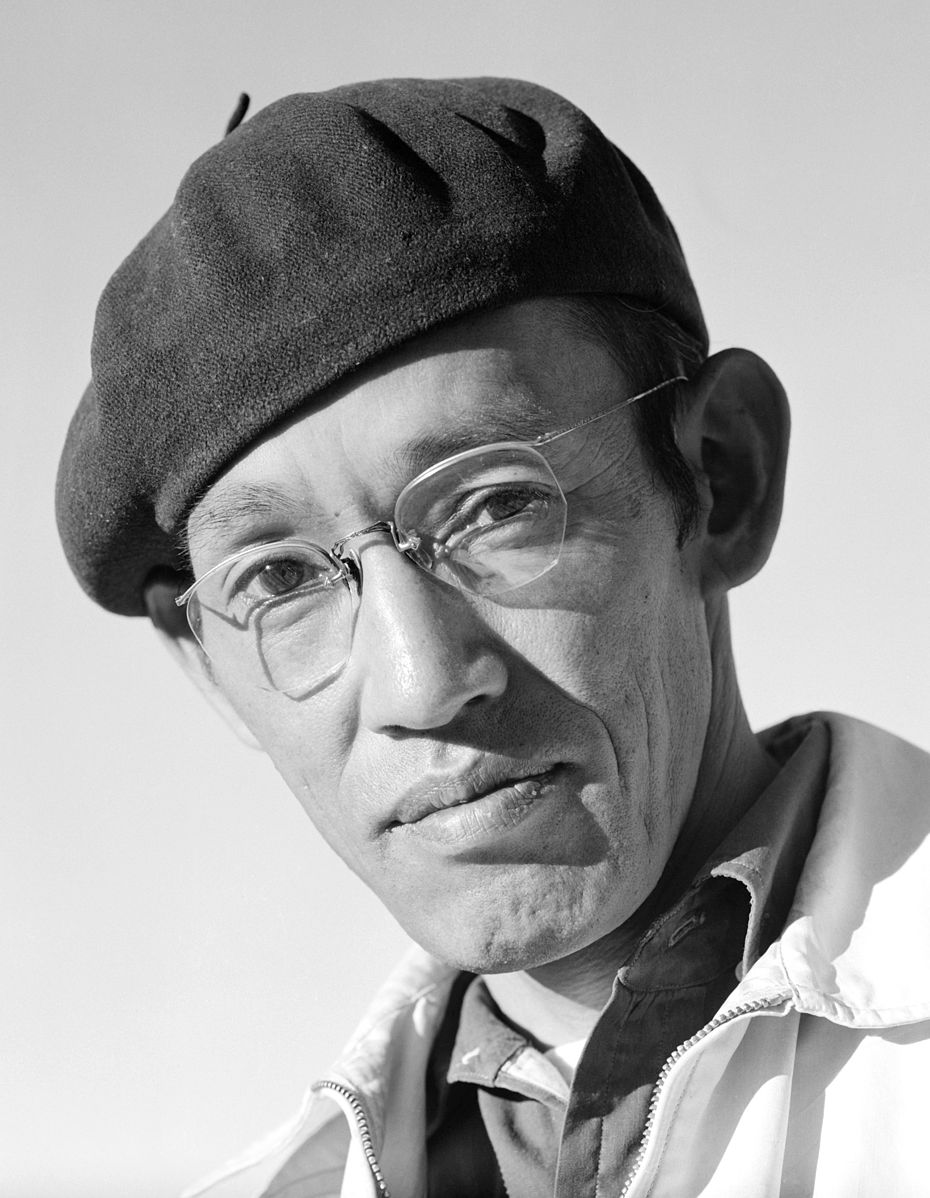 Black and white portrait of photographer Toyo Miyatake. It is a close-up shot of Toyo's face and shoulders. He is looking at the camera and wearing glasses, a black beret, and a light zippered jacket.