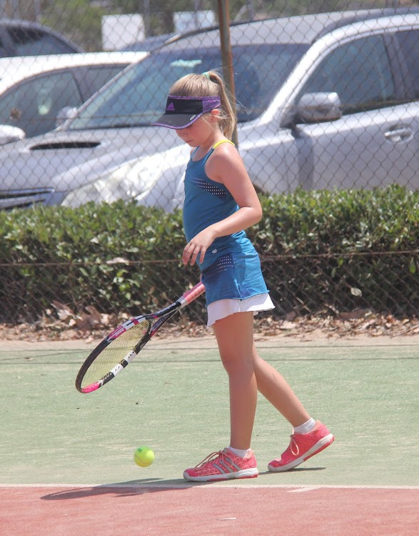 Under-10 girls champion Lacey Bourke prepares to serve on Sunday.