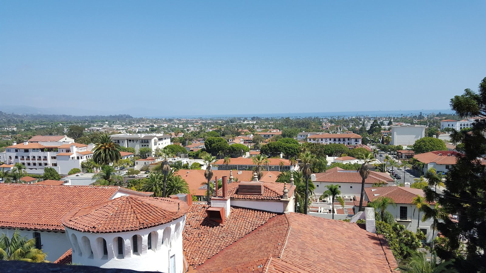 santa barbara whitewashed buildings and tile rooftops and green palm trees with ocean in background california