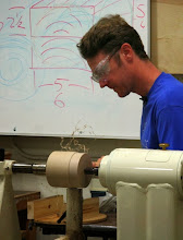 Photo: Mark begins with two dry boards glued together, with a brown paper interface, per the drawing behind him on the board.  The result is sawed into an end-grain cylinder on the band saw and mounted on the lathe between centers, with the centers on the glue line (as seen in the previous photo).  Mark then trues it up so the diameter is equal to the length (to give it a square cross section)...