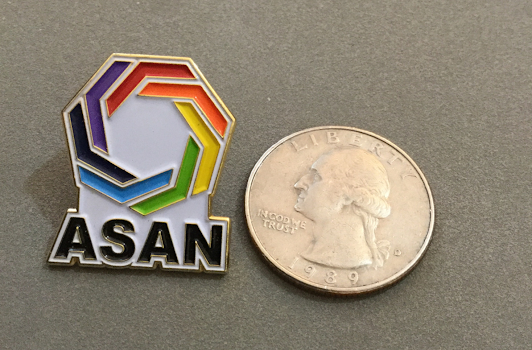 [Image description: An enamel lapel pin with the ASAN logo on it. It is on a grey surface next to a quarter, showing that they are about the same size.]
