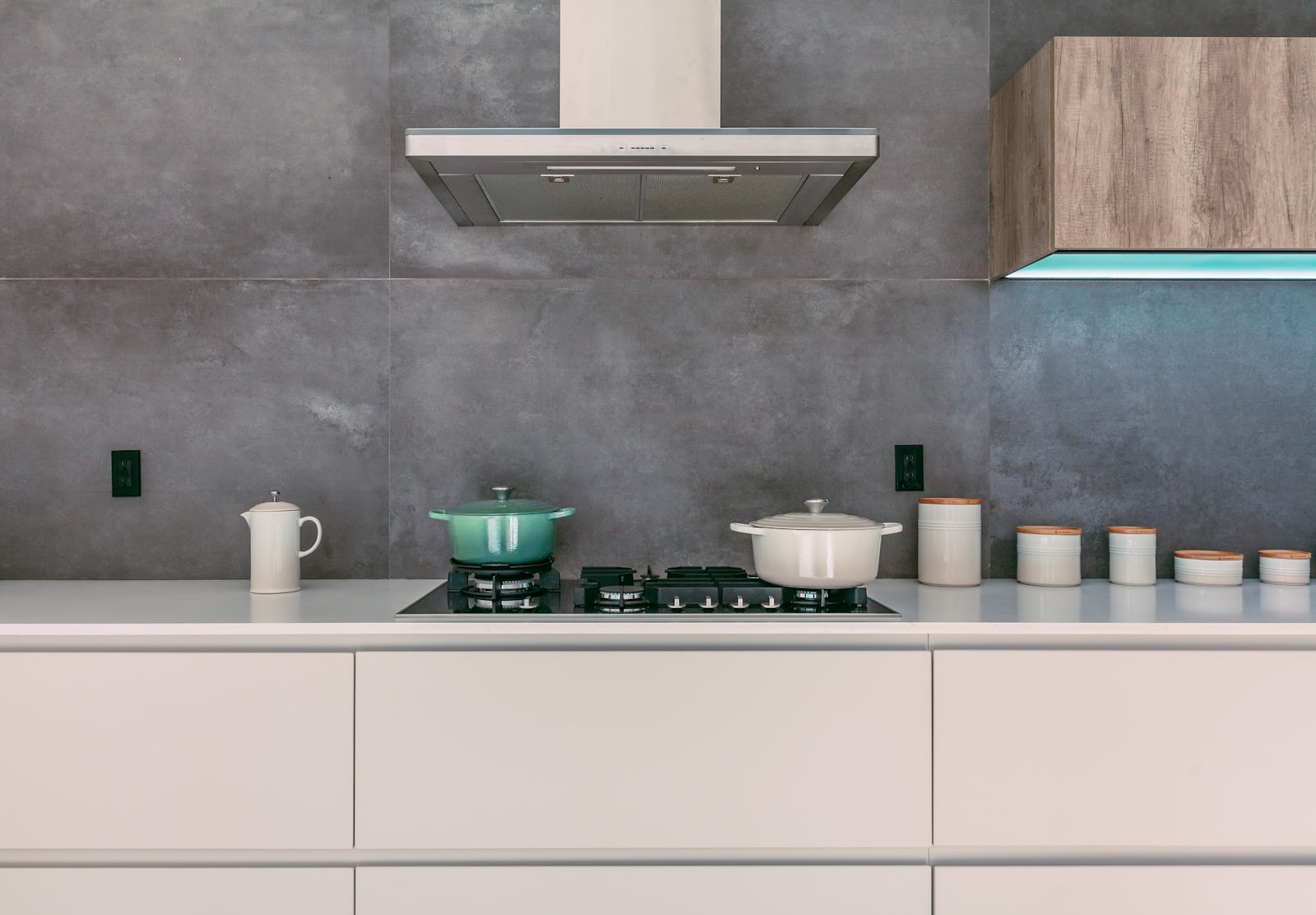 Contemporary handleless kitchen design; handleless drawer, cooker hood and sleek utensils placed in a modern kitchen with grey splashback
