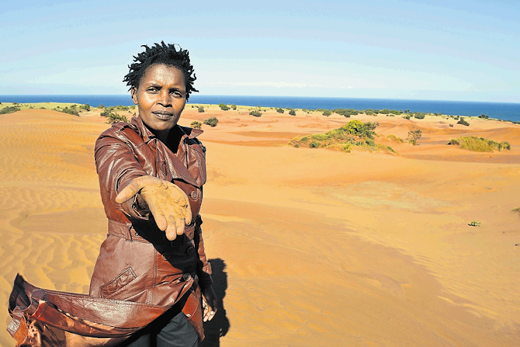 Nonhle Mbuthuma of Amadiba Crisis Committee shows the red sand at Kwanyana Beach near Xolobeni in the Wild Coast that is at the centre of the dune mining dispute. Picture: DAILY DISPATCH/LOYISO MPALANTSHANE