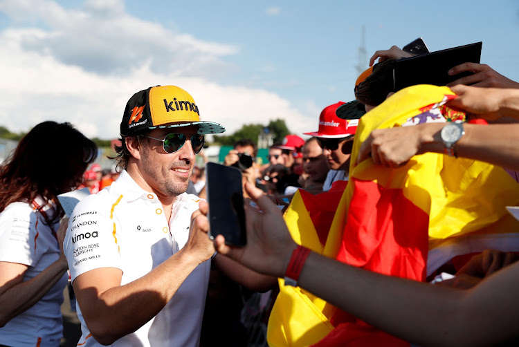McLaren's Fernando Alonso signs his autograph for fans ahead of the Hungarian Grand Prix on July 26 2018 in Budapest.