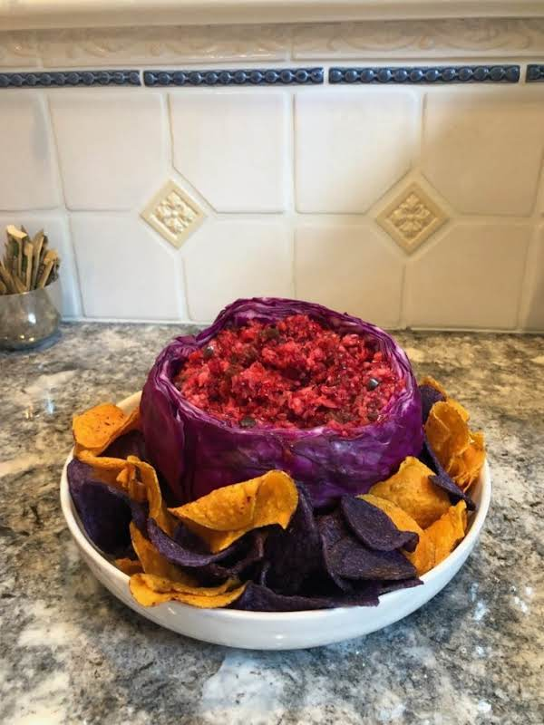 Cranberry Sauce In A Bowl Made Of Red Cabbage, Served With Sweet Potato Chips