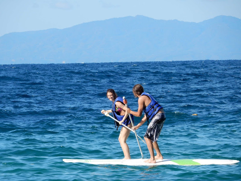 Visitors from Ruby Princess paddleboard in the calm waters of Las Caletas.