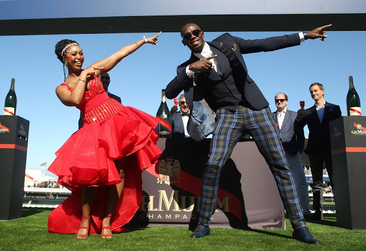 Minnie Dlamini and Olympic champion Usain Bolt at the 2018 Sun Met at Kenilworth Racecourse in Cape Town.