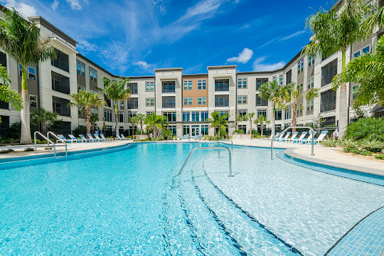 Satori Luxury Apartments resort-style swimming pool with cabanas, a large sundeck, and lounge chairs