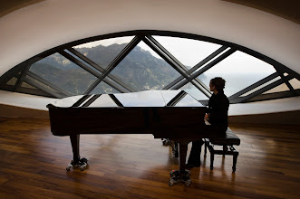 Photo: A pianist plays backstage and looks at the Amalfi coast from Ravello's Auditorium Oscar Niemeyer the day of its official inauguration on January 29, 2009. After ten years of controversy, the auditorium, designed by Brazilian architect Oscar Niemeyer opens in the southern Italian town of Ravello on the Amalfi coast.  AFP PHOTO / ROBERTO SALOMONE   TO GO WITH AFP STORY BY KELLY VELASQUEZ (Photo credit should read ROBERTO SALOMONE/AFP/Getty Images)