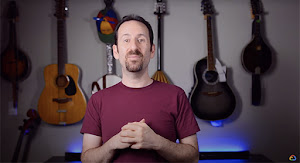 Man standing in front of guitars and a Google hat facing the camera.