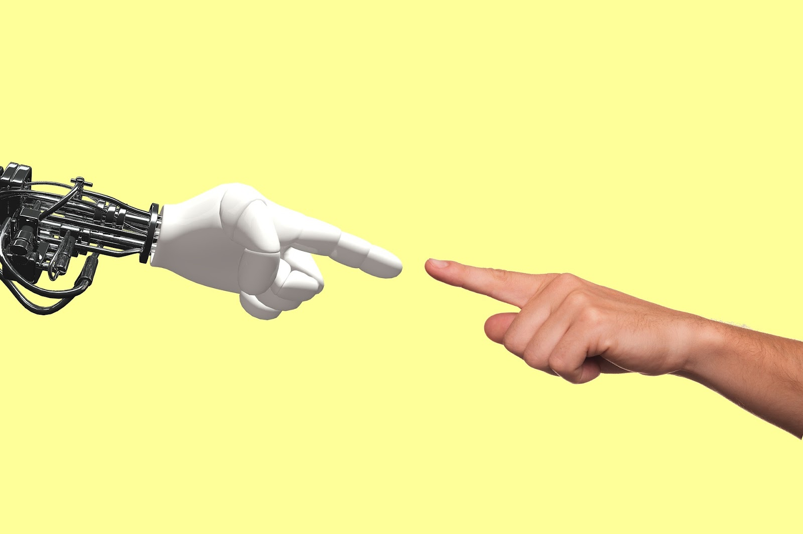 A white robotic hand reaches out to touch the tip of the index finger of a genuine human hand over a yellow background.